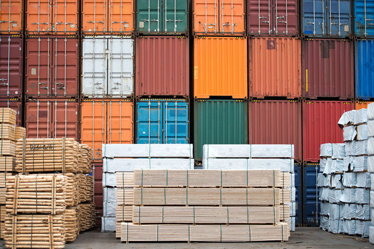 Containers and neatly stacked timber stock. Business Container Delivery Distribution Goods Harbor Industry Transport Transportation Cargo Comercial Dock Export Import Loading Logistic Material Pallets Port Stacked Storage Terminal Unloading Warehouse