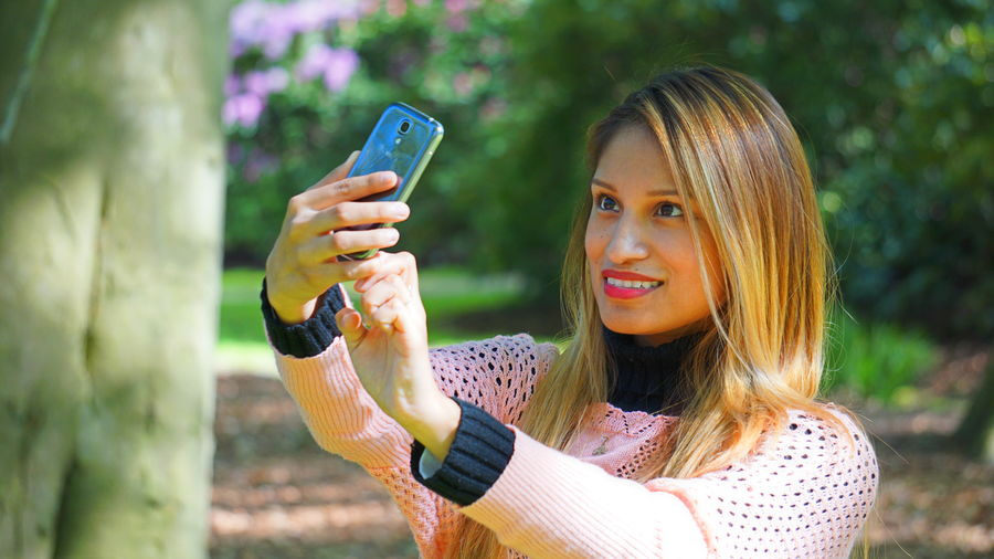 Close-up of woman taking selfie through phone at park