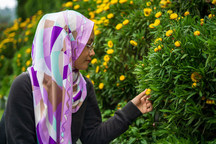 Side view of woman holding purple flower