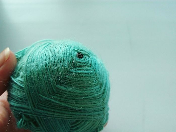 Close-Up Of Hand Holding Green Wool Ball Against Colored Background