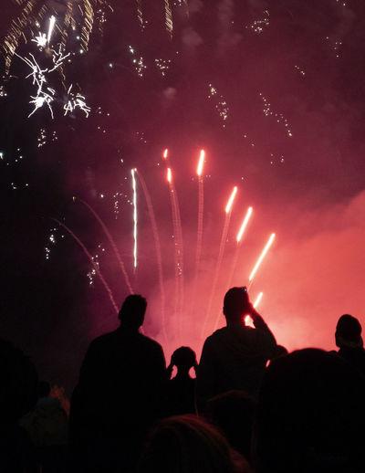 Silhouette people watching firework display