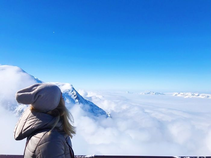 Side view of woman looking at snowcapped mountains against blue sky
