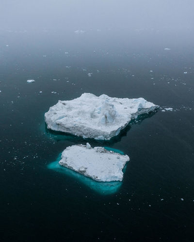 Water Cold Temperature Sea Winter Snow Ice Nature No People Frozen Iceberg - Ice Formation Beauty In Nature Day Tranquility Glacier Outdoors Environment Scenics - Nature Land Floating On Water Iceberg Greenland Fog Mist