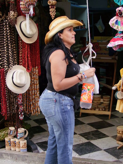 Cuban Shop Owner Business Casual Clothing Choice Cuba, Havana, Woman, Shop, Retail Cultures Fashion Front View Holding Leisure Activity Lifestyles Looking At Camera Portrait Real People Standing Three Quarter Length Women Young Adult