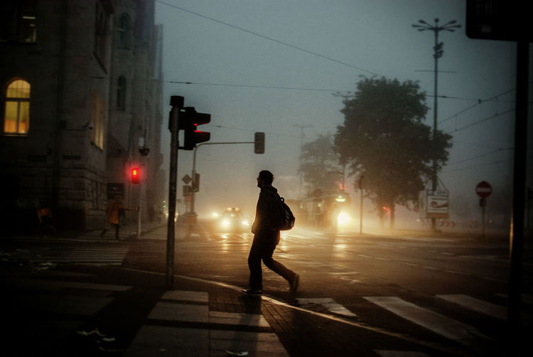 Full Length Of Man Crossing City Street At Dusk During Foggy Weather