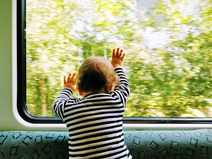 Rear View Of Baby Boy Touching Window While Traveling In Train