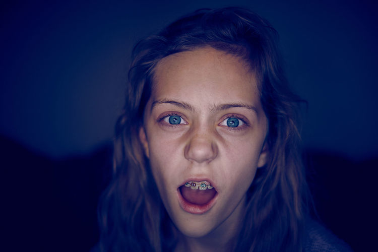 Close-up of girl with mouth open in darkroom