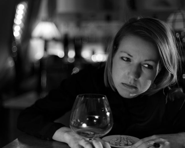 Thoughtful mid adult sitting by food and drink on table in restaurant