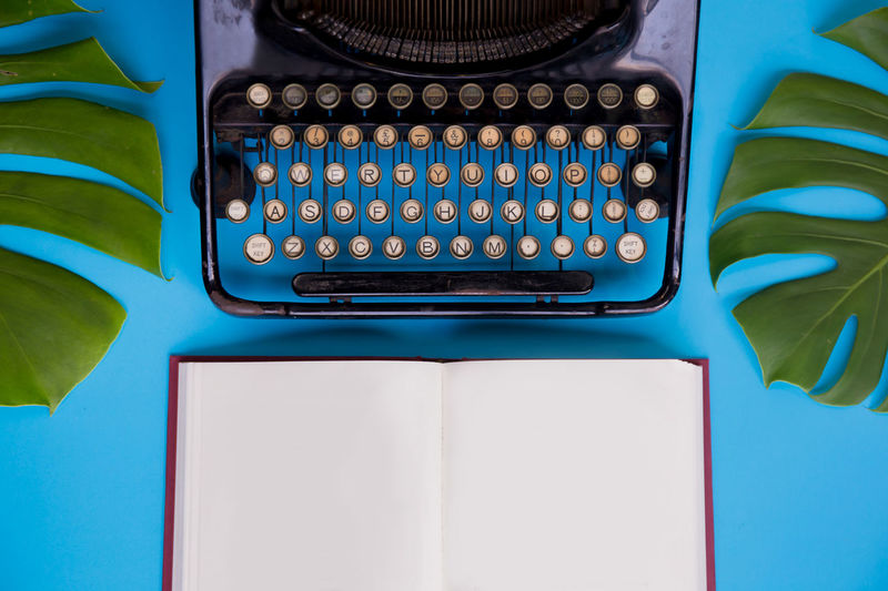 Close-Up Of Typewriter And Book Against Blue Background