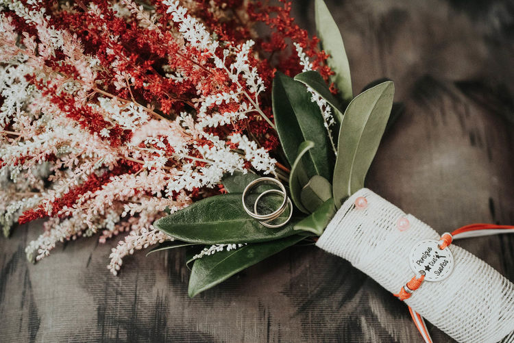 High Angle View Of Flowers With Wedding Rings On Table