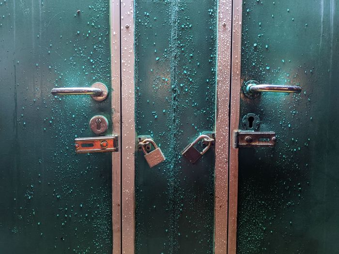 The condition of an unlocked door in an employee rest area after rain.