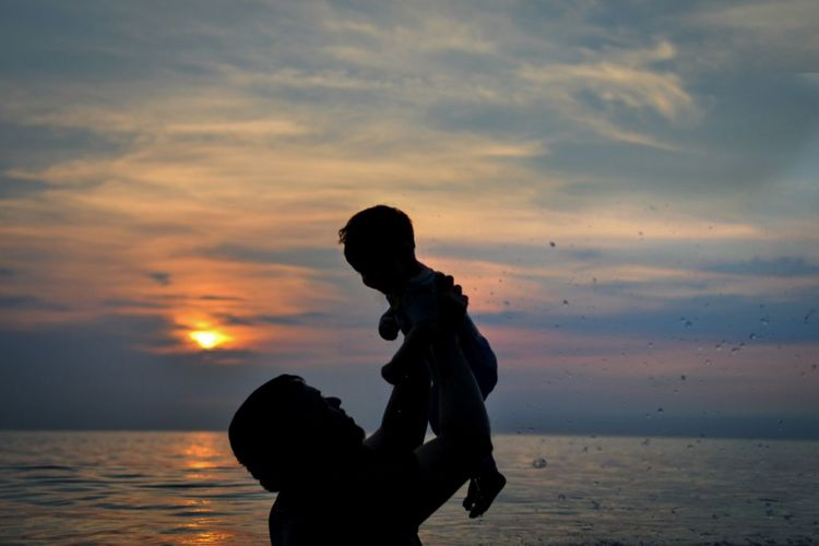 Silhouette man with toddler son at beach against sky during sunset