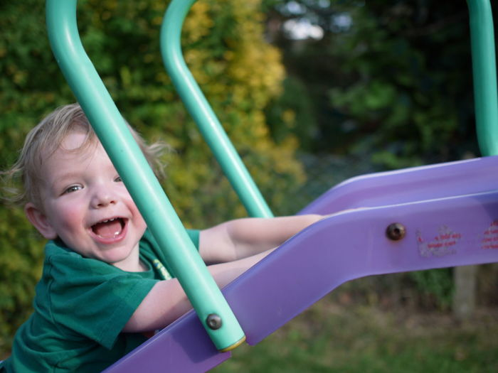 Portrait Of Cute Baby Boy On Slide At Playground