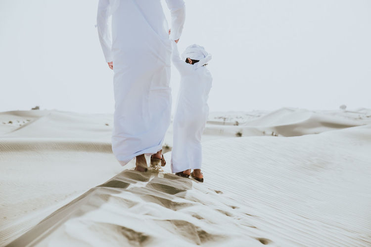 Low section of father with son enjoying while walking in desert