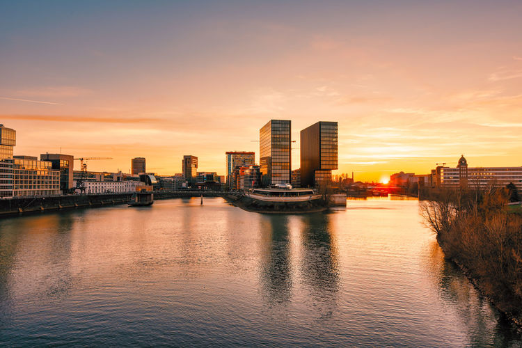 Duesseldorf, GERMANY - February 25, 2019: The modern buildings of the new media harbor gloom in the sinking sun light Architecture Building Exterior Built Structure City Sky Sunset Water Building Urban Skyline Cityscape Nature Transportation Office Building Exterior No People Landscape Cloud - Sky Reflection Skyscraper River Outdoors Modern Passenger Craft