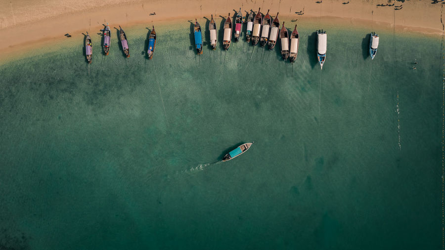 Top view of long tail boat passengers travel tourists on the beach iat ao nang railay krabi thailand