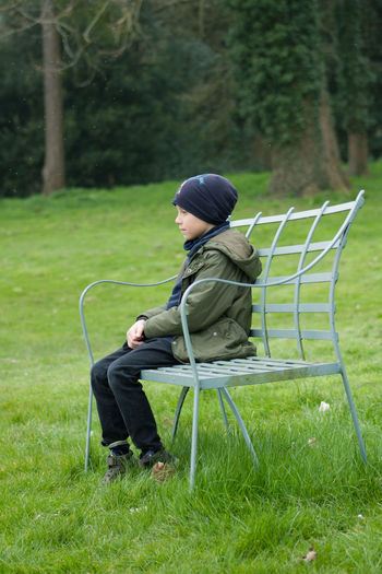 Side view of man sitting on chair in field