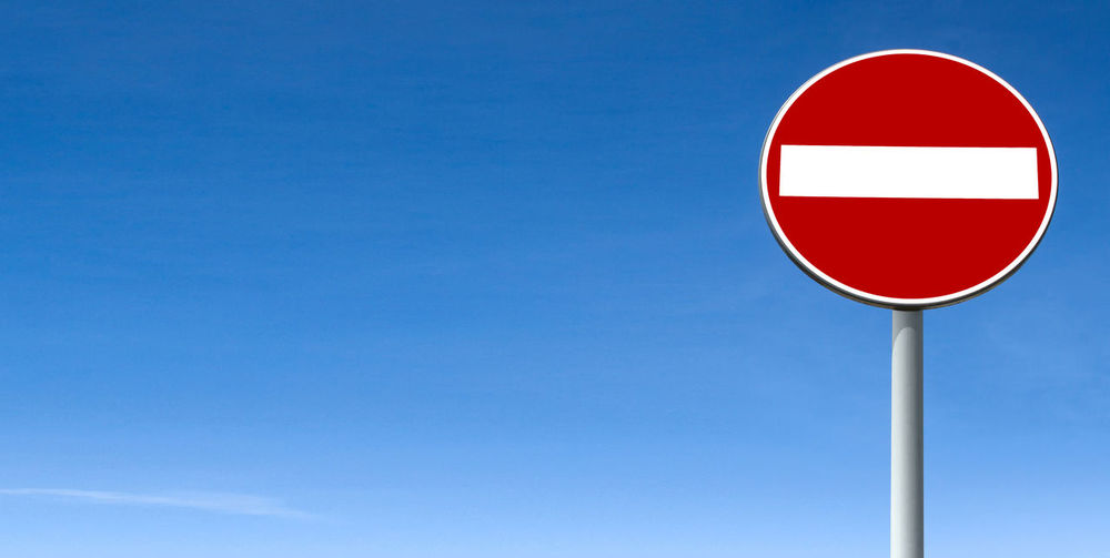 Road sign against clear blue sky