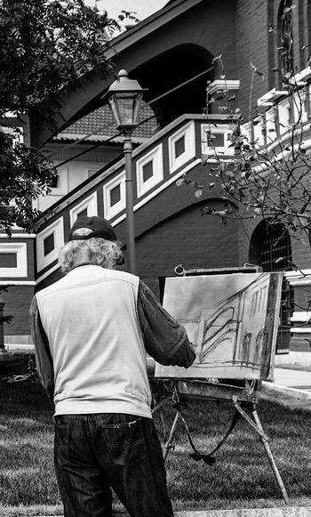 Rear View Of Artist Painting On Canvas While Standing Against Building