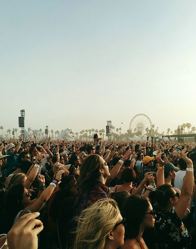 People enjoying at concert against clear sky
