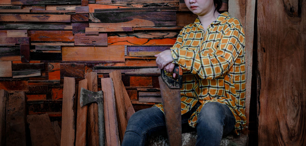 Carpenter women sitting with hold saw at old wood wall background