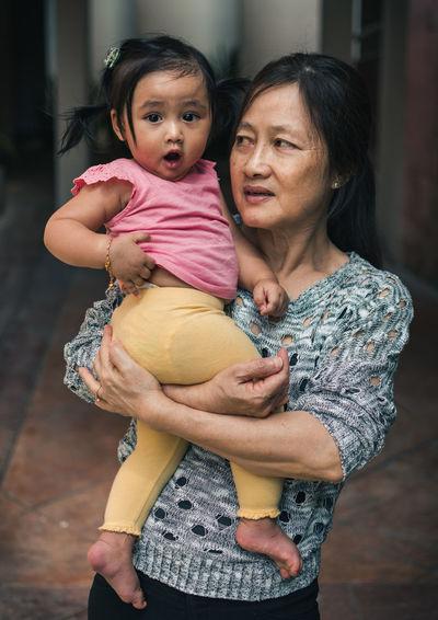 Grandmother Carrying Granddaughter