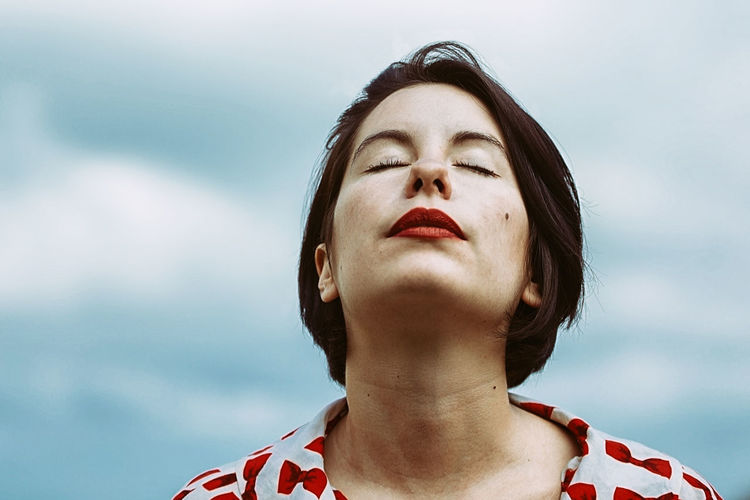 Young woman with eyes closed against sky