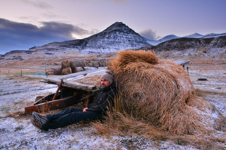 Man looking away while relaxing by hay bale at field