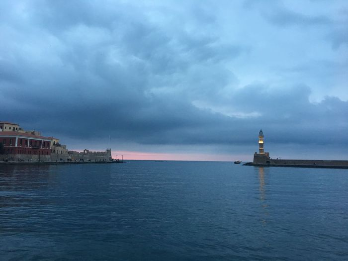 Lighthouse on sea against buildings