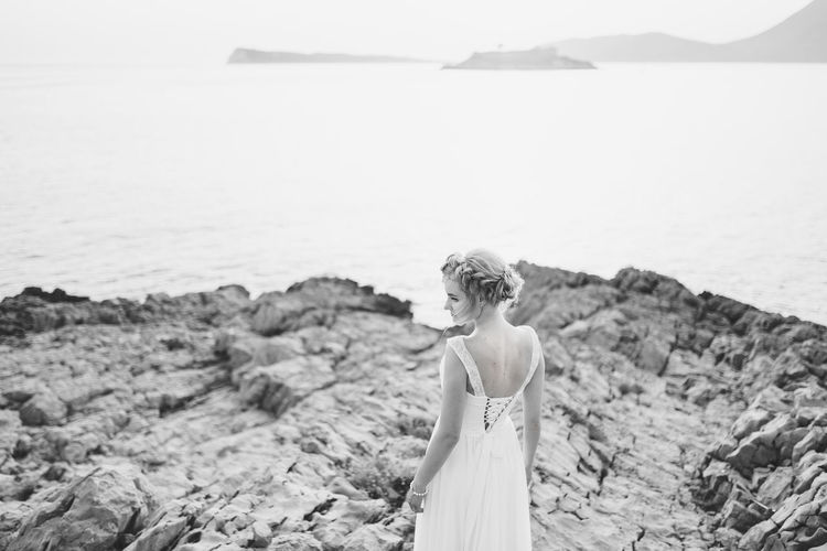 Rear view of woman standing on rock against sea