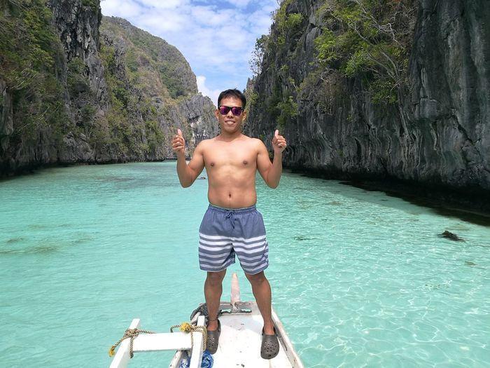 Portrait Of Smiling Shirtless Man Showing Thumbs Up While Standing On Ship Bow On Sea
