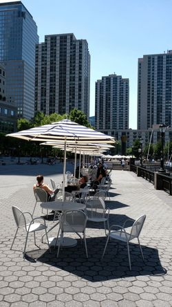Relaxing on the NY waterfront. Tables And Chairs Fuji Xt20 Plaza Umbrellas Photography NYC Landscape Sunlight And Shadow People Wide Open Spaces Sky Buildings City Tree Sitting Chair Clear Sky Outdoor Chair Relaxation Sunshade
