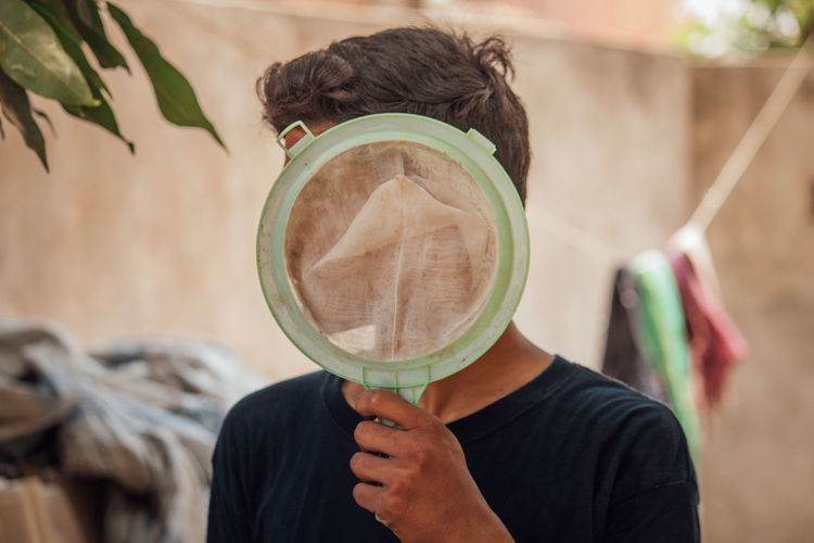 Close-up of man holding strainer while standing against wall