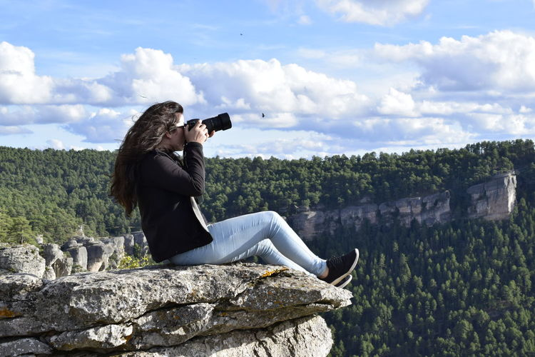 Side view of woman photographing on rock