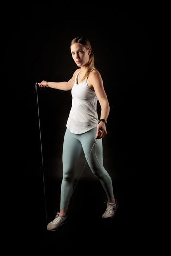 Young woman looking away while standing against black background Adult Sport Activity Athletic Attractive Beautiful Body Exercise Female Fit Fitness Girl Gym Health Healthy Lifestyle Muscle One person Pilates Pose Slim Sportswear Studio Training Weight Wellness Woman Workout Young Black Background Studio Shot One Person Full Length Indoors  Young Adult Young Women Cut Out Looking At Camera Portrait Lifestyles Confidence  Standing Holding Women Healthy Lifestyle Front View Beautiful Woman