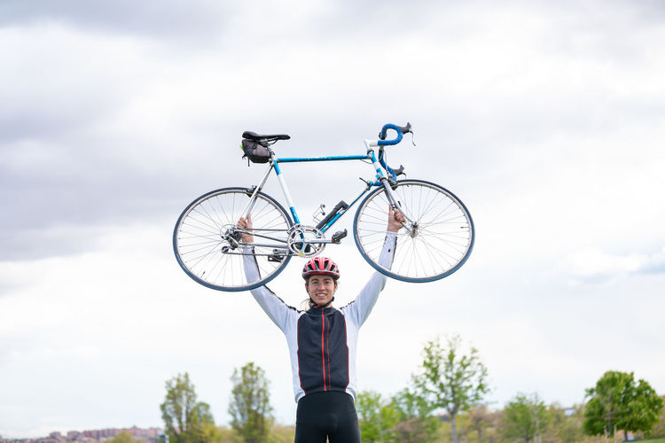 Low angle view of man holding bicycle against sky