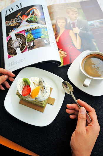 Cropped Image Of Hand With Cake And Coffee On Table In Restaurant