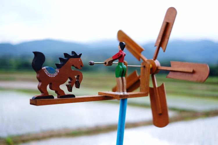 Close-up of figurine on wooden pinwheel toy with agricultural field