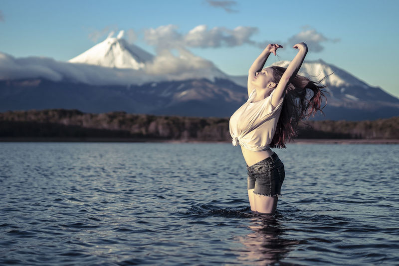 Adult Arms Raised Beautiful Woman Beauty In Nature Hairstyle Human Arm Leisure Activity Lifestyles Mountain Mountain Range Nature One Person Outdoors Real People Scenics - Nature Sky Standing Tranquil Scene Tranquility Water Waterfront Women Young Adult