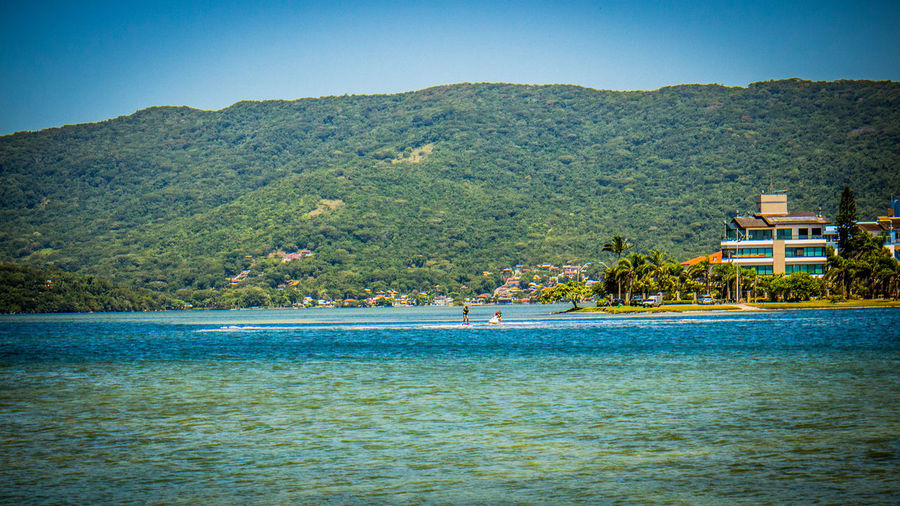 Lagoa Da Conceição Architecture Beach Beauty In Nature Blue Blue Sky Clear Sky Day Florianópolis Brasil Holiday Landscape Mountain Nature No People Outdoors Sea Sky Tranquility Tree Vacations Water Waterfront