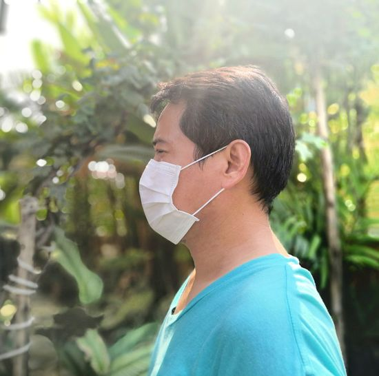 Side view of man wearing surgical mask against trees