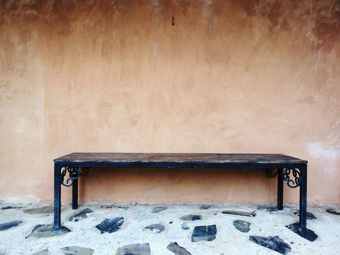 Empty bench on table against wall