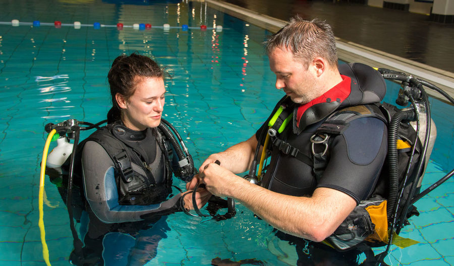 Full Length Of Man And Woman Scuba Diving In Swimming Pool