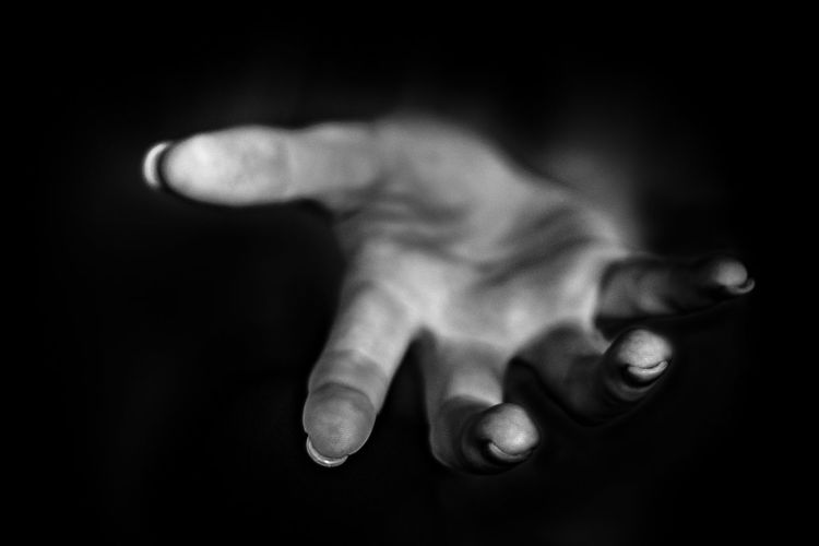 Close-Up Of Human Hand Against Black Background
