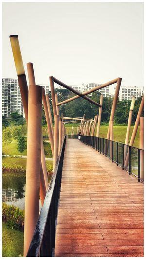 Footbridge leading to water against clear sky