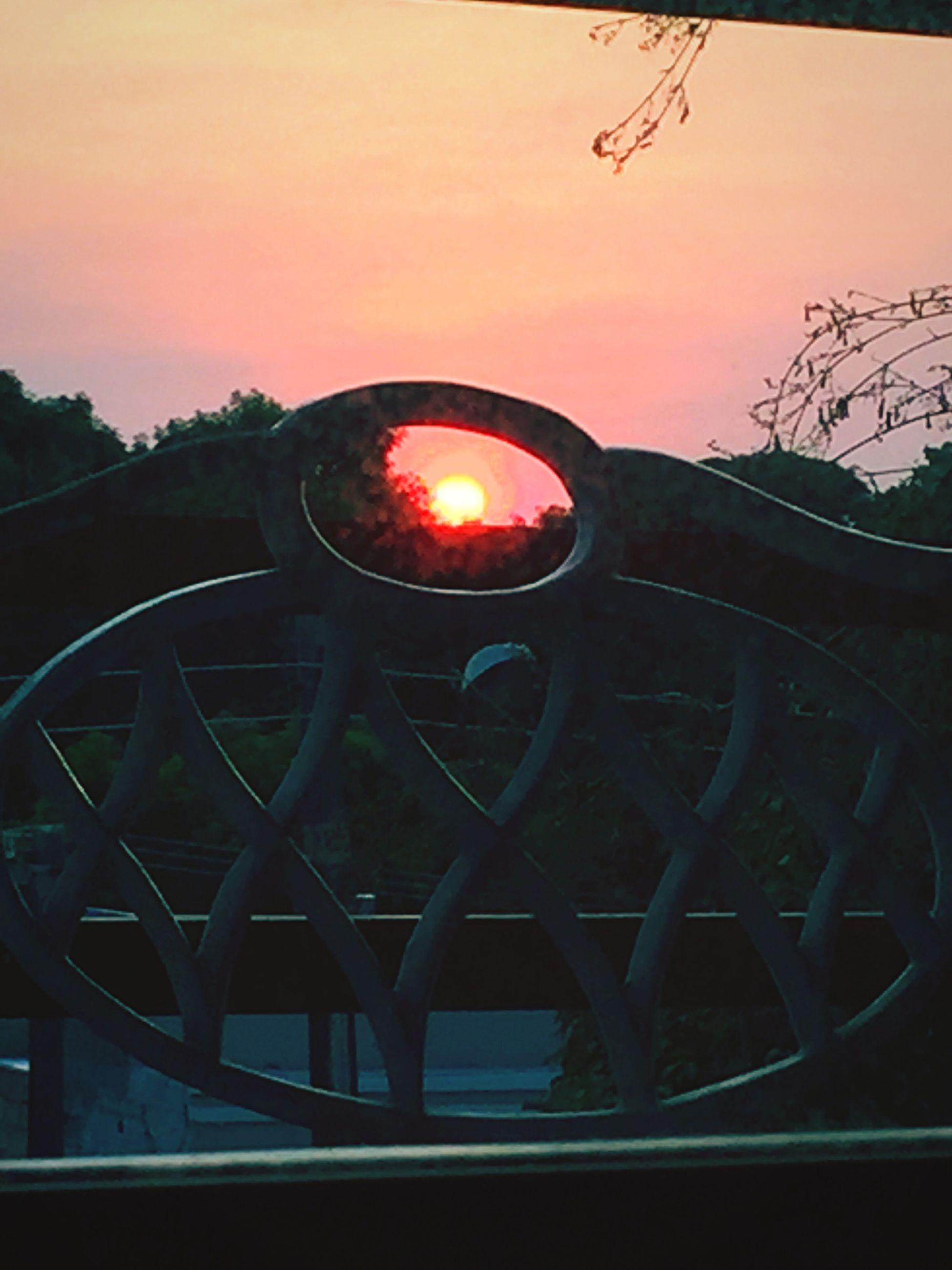 sunset, illuminated, orange color, sky, sun, silhouette, transportation, lighting equipment, circle, glowing, tree, connection, street light, no people, outdoors, night, built structure, metal, bridge - man made structure, railing