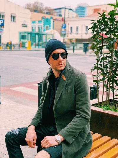 Man wearing sunglasses sitting outdoors