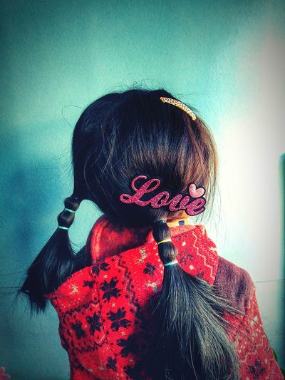 Rear view of girl with pigtails and love clip in hair while standing against wall