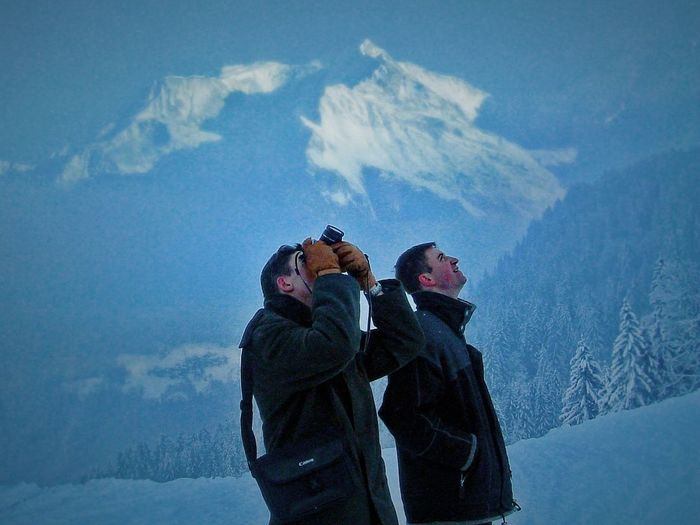 Mid Adult Man By Friend Photographing On Snowcapped Mountain