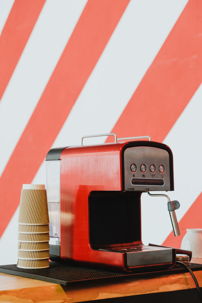 Close-up of coffee maker on table against wall